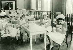 Four nurses, wearing face masks, feeding babies, c1940s