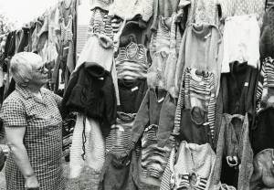 Photo of Mrs Hall with garments made by the Golden Needle League, 1979