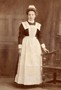 A girl who has completed her training and is ready, with her uniform, to go out to work in domestic service, 1910