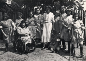Group photo of a teacher and ten girls, one of whom is in a wheelchair and another is using a crutch; St Nicholas' Orthopaedic Hospital and School, Pyrford, Surrey [1917]