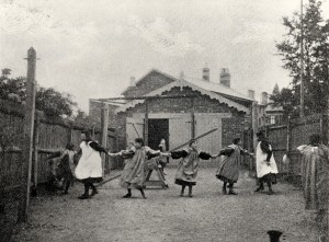 Seven girls playing 'ring-a-ring of roses' in the back yard of this home, 1897