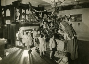 Children in a Society home in the 1940s receive a present from Father Christmas