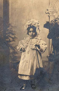 Little girls' clothing could be highly decorative, like the frilly bonnet and dress with pom-poms shown in this photograph. This three-year old girl was placed with foster parents in the Devonshire countryside. Finding foster homes for children was always a key area of the Waifs and Strays' Society's work.