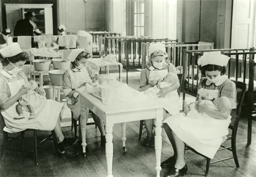 Four nurses, wearing face masks, feeding babies
