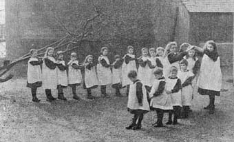 Two older girls form the archway for this game of 'oranges and lemons'. This game, which originated in the 17th century, was played by singing the popular nursery rhyme while children danced in line through the archway. It ended when the children forming the archway let their arms fall down around one 'captured' child.