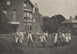 Girls playing Ring-a-ring-a-roses in the back garden of the Loughton home. Playgrounds used to be full of the sounds of singing games like this. The song 'Ring-a-ring-a-roses' was actually based on the unpleasant events of the Black Death in London during 1665 - when people would wear posies of flowers to hide the stench of the plague.