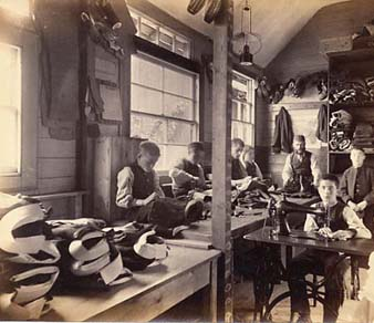 Larger workshops were run as a production line, with several different jobs involved. The boys on the left are hand sewing, while the boy in the foreground is using a treadle sewing machine.