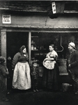 Adults and children outside an ironmongers